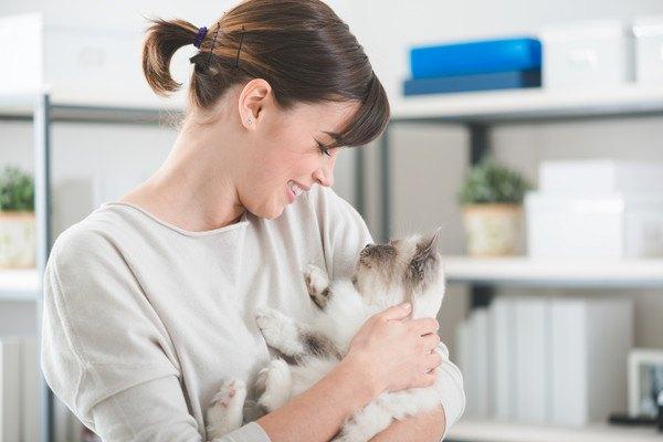 女性に抱っこされる爪が黒いかも知れない白い猫