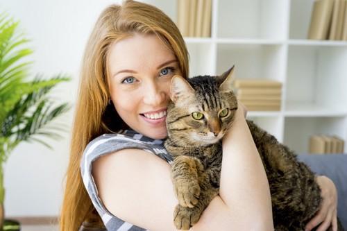 笑顔で猫を抱きしめる女性