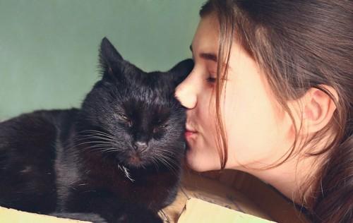 目を閉じた黒猫にキスをする女性