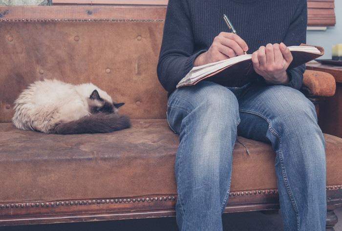 日記を書く男性と猫