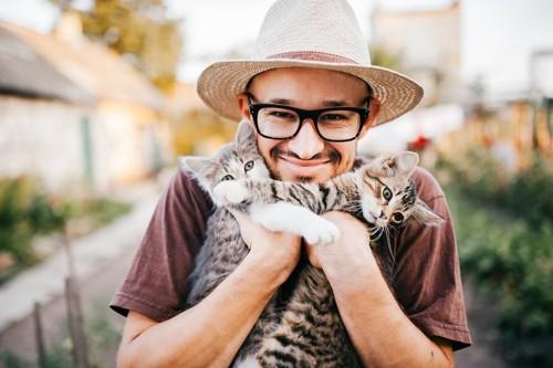 2匹の猫を抱えている笑顔の男性