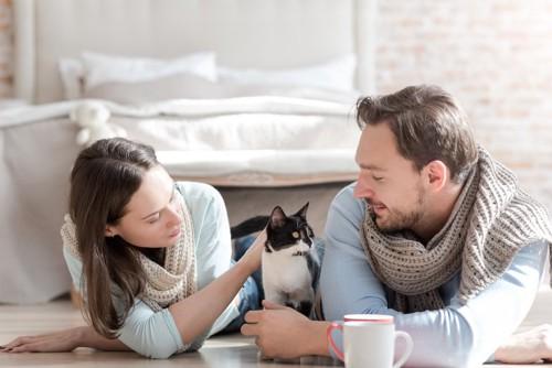 くつろぐカップルの間に入る猫