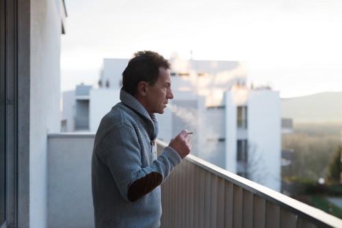 ベランダでたばこを吸う男性