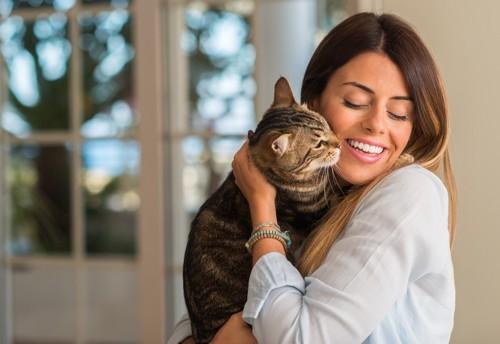 目をつぶり笑う人と猫