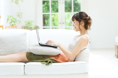 ソファーでパソコンを使う女性