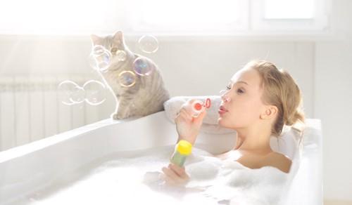 お風呂の縁にいる猫と入浴の女性