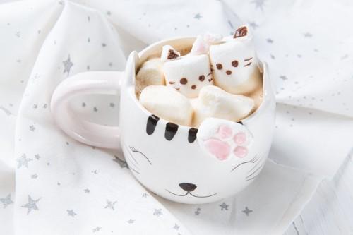 カップに入った普通のマシュマロと猫の顏を描いたマシュマロ