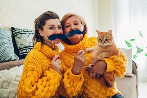 にぎやかな二人の女性と抱かれる猫