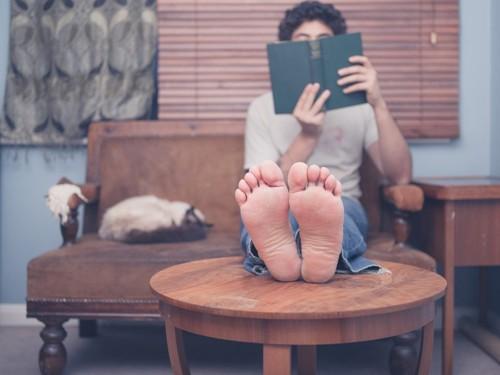 裸足で本を読む人と猫