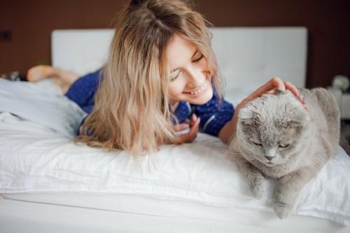 ベッドの上で猫を撫でる女性