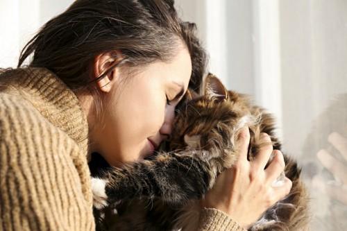 額をくっつけ合う猫と女性