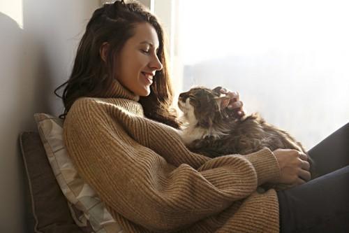 女性と抱っこされる猫