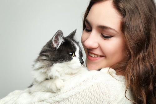 笑顔の女性に抱っこされている猫