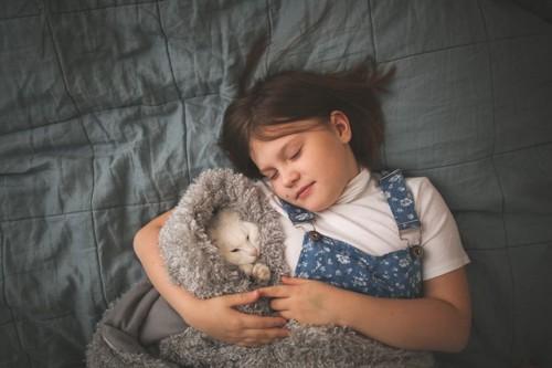 猫と一緒に寝る女の子