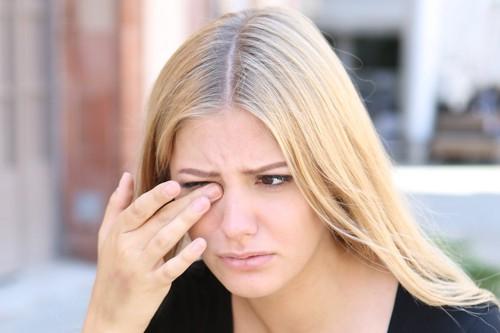 アレルギーで目が痒そうな女性