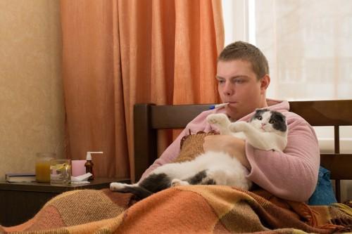 猫を抱きながら体温計をくわえる男性