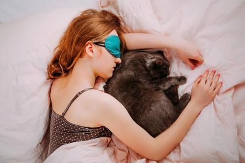 アイマスクをして眠る女性と一緒に眠る猫