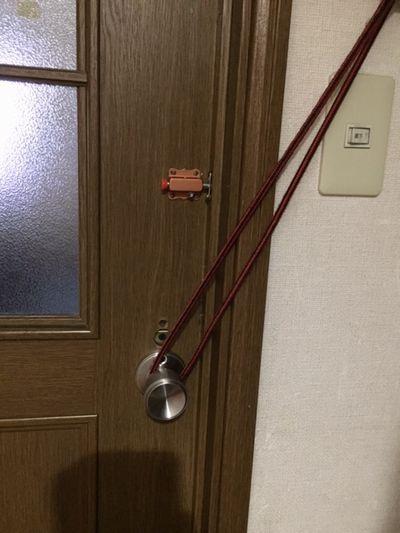 円筒錠のドアノブに紐を掛けている