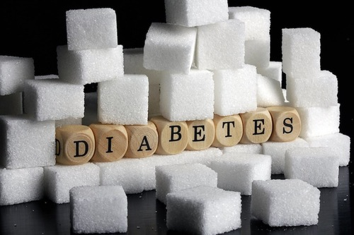 山積みにされた角砂糖と糖尿病の文字