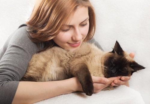 寝ている猫を抱きしめる女性