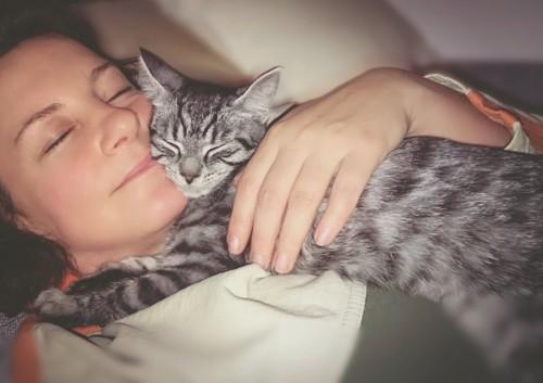 子猫を抱きしめて一緒に眠る女性