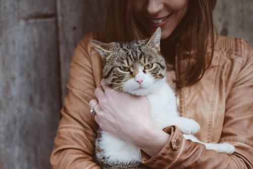 笑顔の女性に抱かれている猫