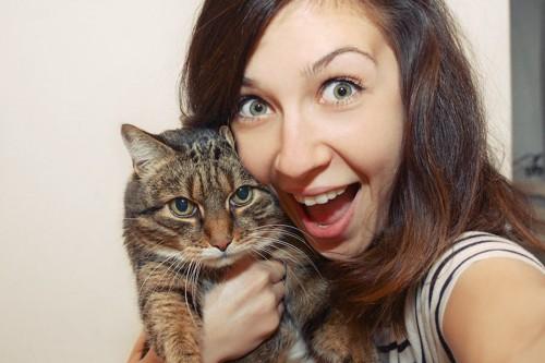 猫を抱き上げて顔を近づける女性