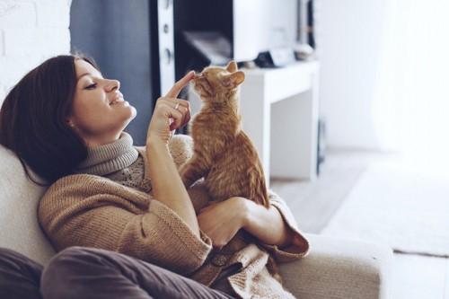 女性に抱かれた猫