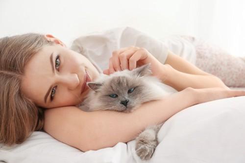 女性と横になる猫