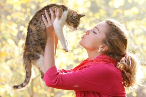 猫を抱き上げている女性