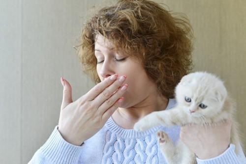 猫を抱っこしながら咳をする女性
