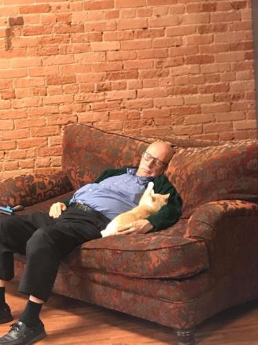 ソファで寝るおじいちゃんと黄色の猫