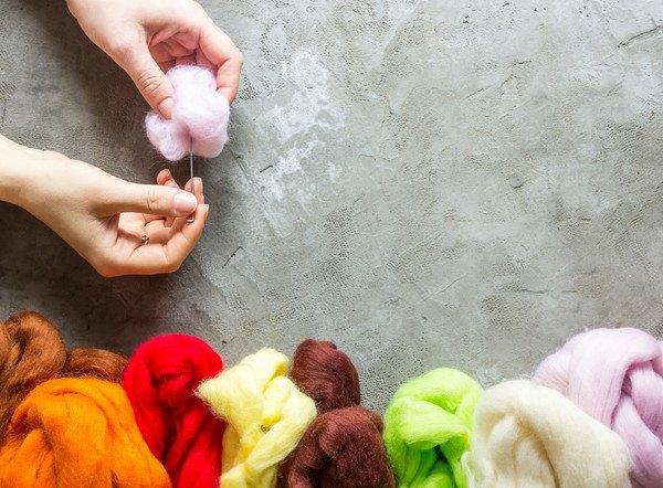 カラフルな羊毛とニードルを持つ手