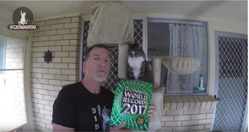 ギネスブックを持つ男性と猫