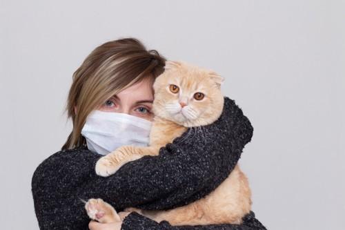 マスクをした飼い主と猫