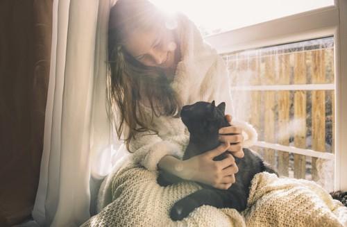 女性と見つめ合っている黒猫