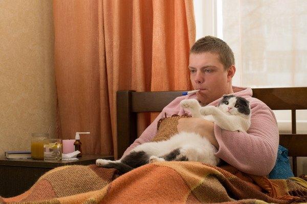 病気の男性と猫