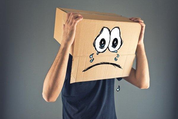 悲しい表情が描かれた段ボールをかぶる