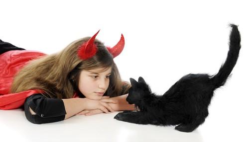 ハロウィンの衣装を着た女の子と黒猫