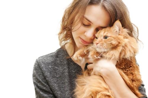 目を閉じて猫を抱きしめる女性