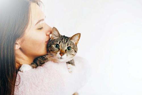 猫を抱っこして顔を近づける女性