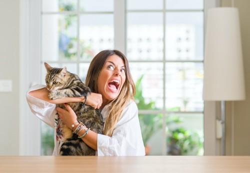 猫を抱きながら大声で騒いでいる女性