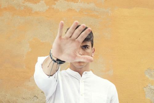 手をかざして顔を隠す男性