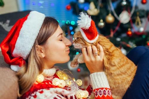 サンタの帽子を被った女性とキスをする茶トラ猫