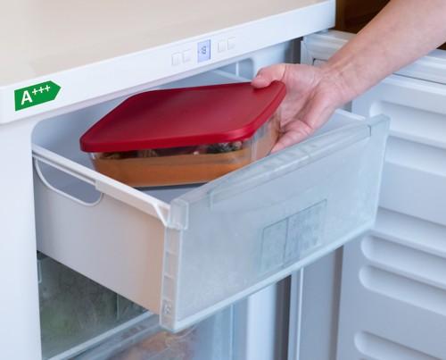 冷凍庫に料理を保存する人