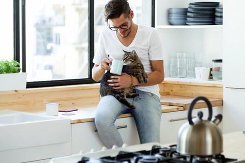 コップを持つ男性と猫