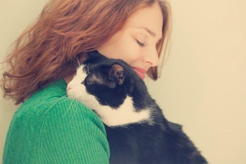 飼い主に寄り添って寝る猫