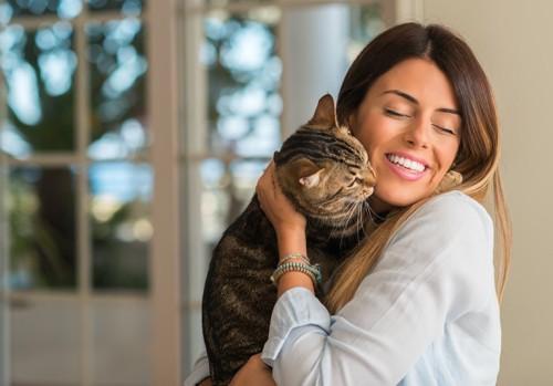 女性に抱かれて顔を近づける猫
