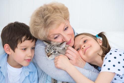 猫を抱きしめる年配の女性と寄り沿う二人の子供