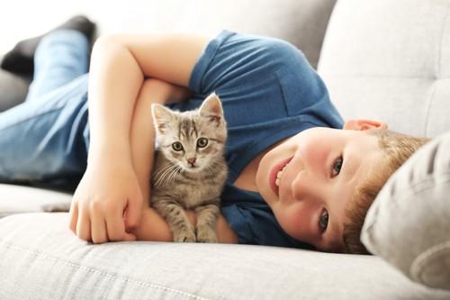 ソファーの上で子猫を抱く男の子